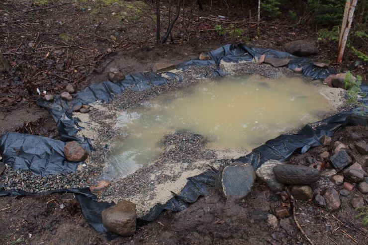 The filled pond with brown water from the sand residue